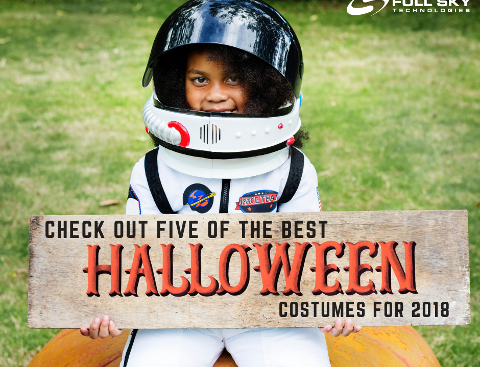 Kid in an astronaut costume holding sign that says Check Out Five of the Best Halloween Costumes for 2018
