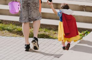 Parent walking child during trick-or-treating. Child is wearing a Snow White costume.