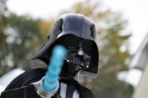 Darth Vader Halloween Costume with light saber pointing at camera
